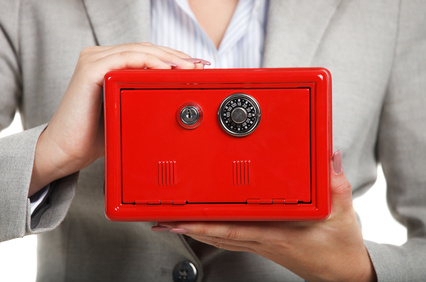 Businesswoman holding red safe in her hands