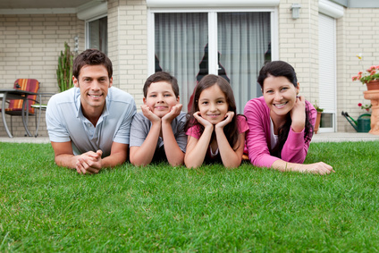 Portrait of family of four lying in backyard