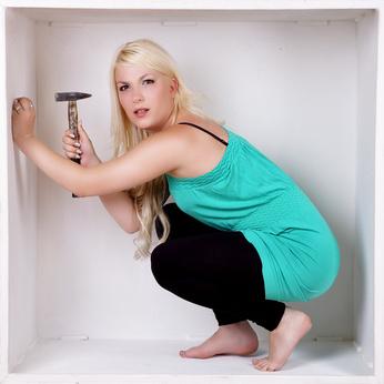 Frau mit Hammer in einem Würfel