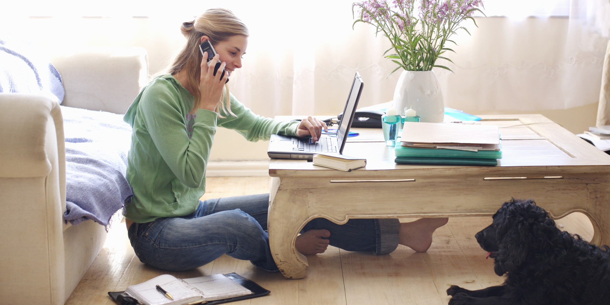 Mid adult woman sitting on floor, leaning on sofa, talking on, using laptop, side view