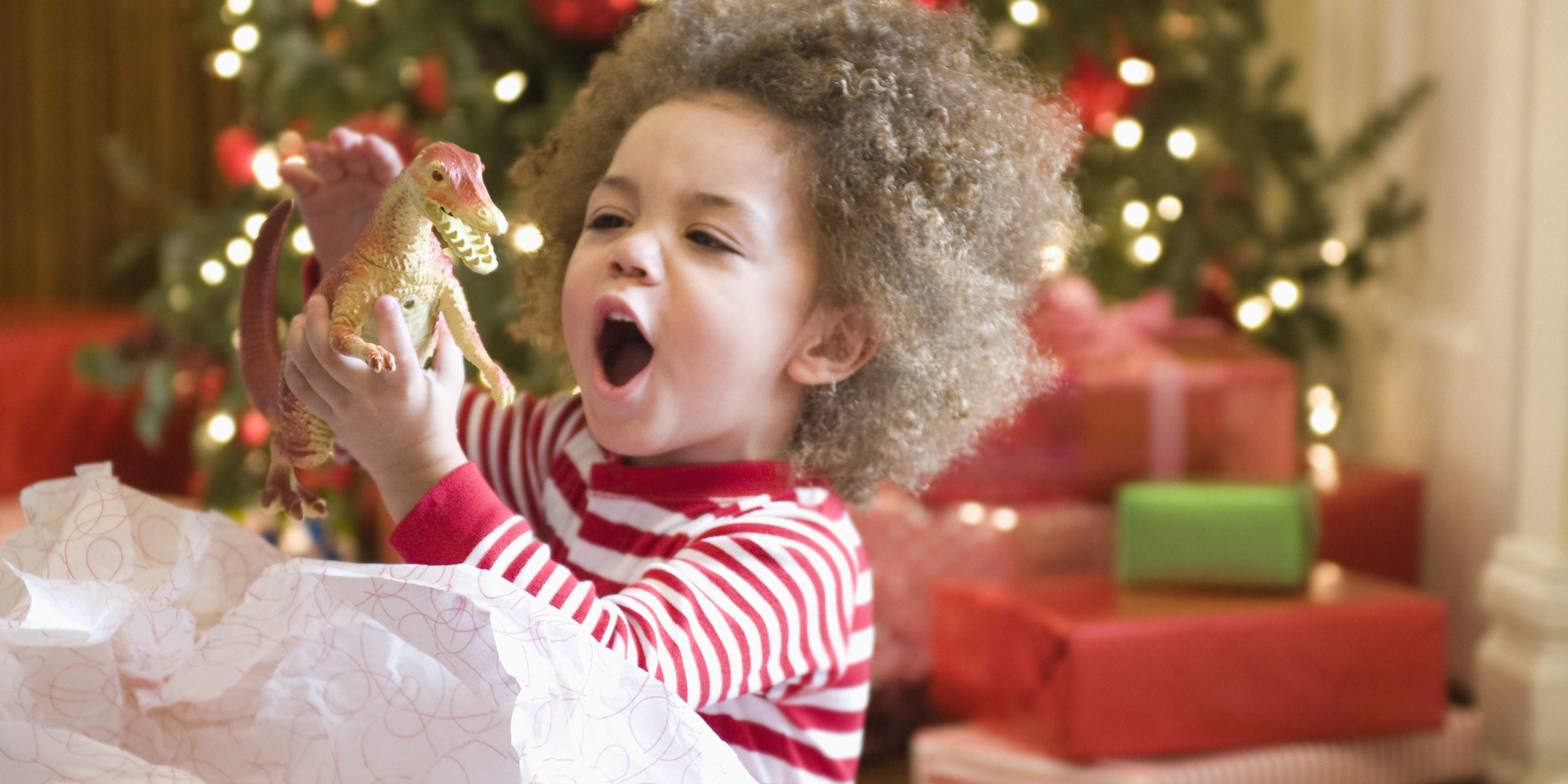 Mixed race boy playing with Christmas gift