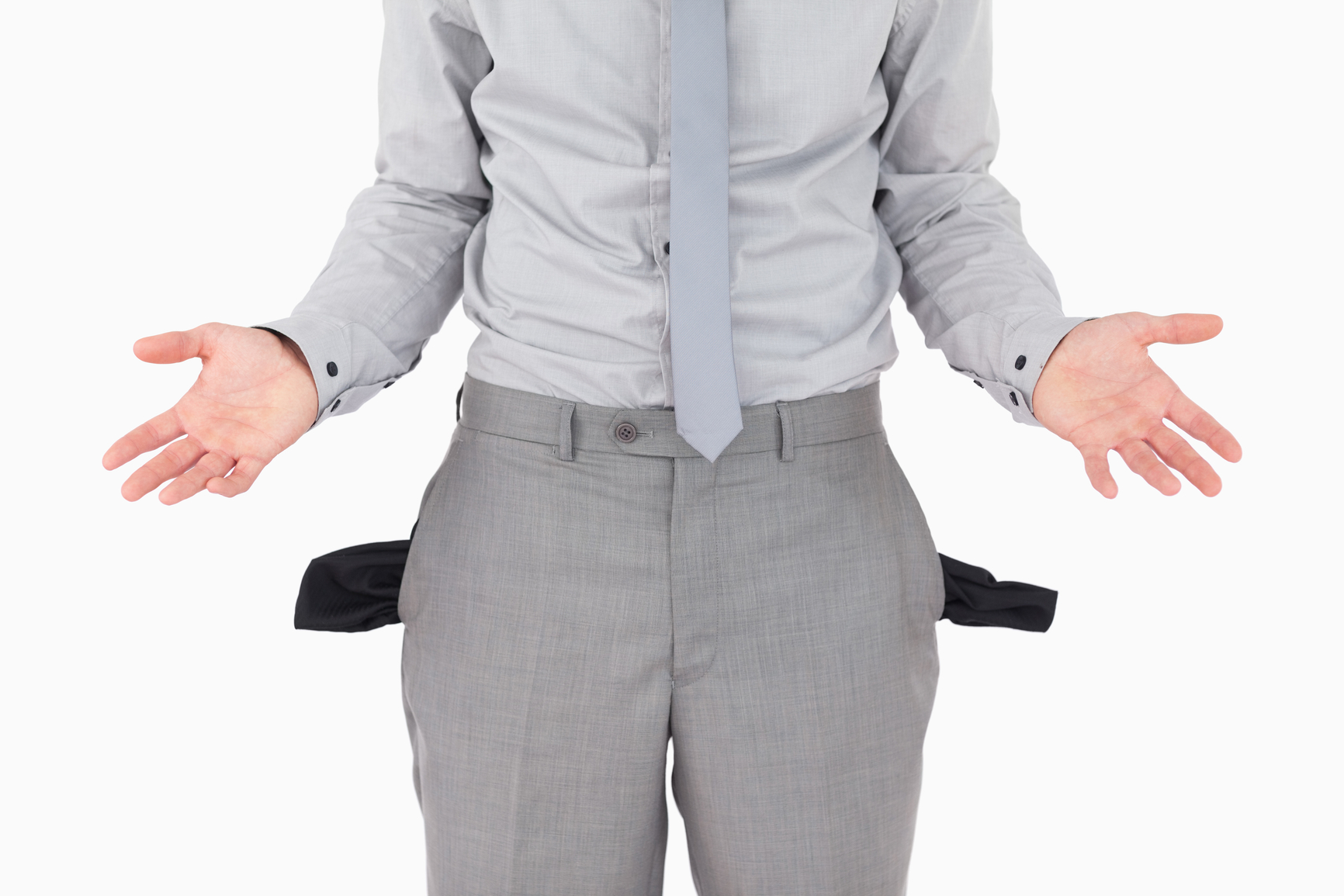 Broke businessman with empty pockets against a white background