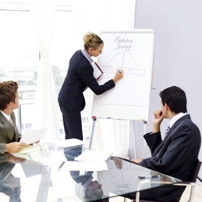 Businesswoman Writing on White Board and Businessman at Table --- Image by © Royalty-Free/Corbis