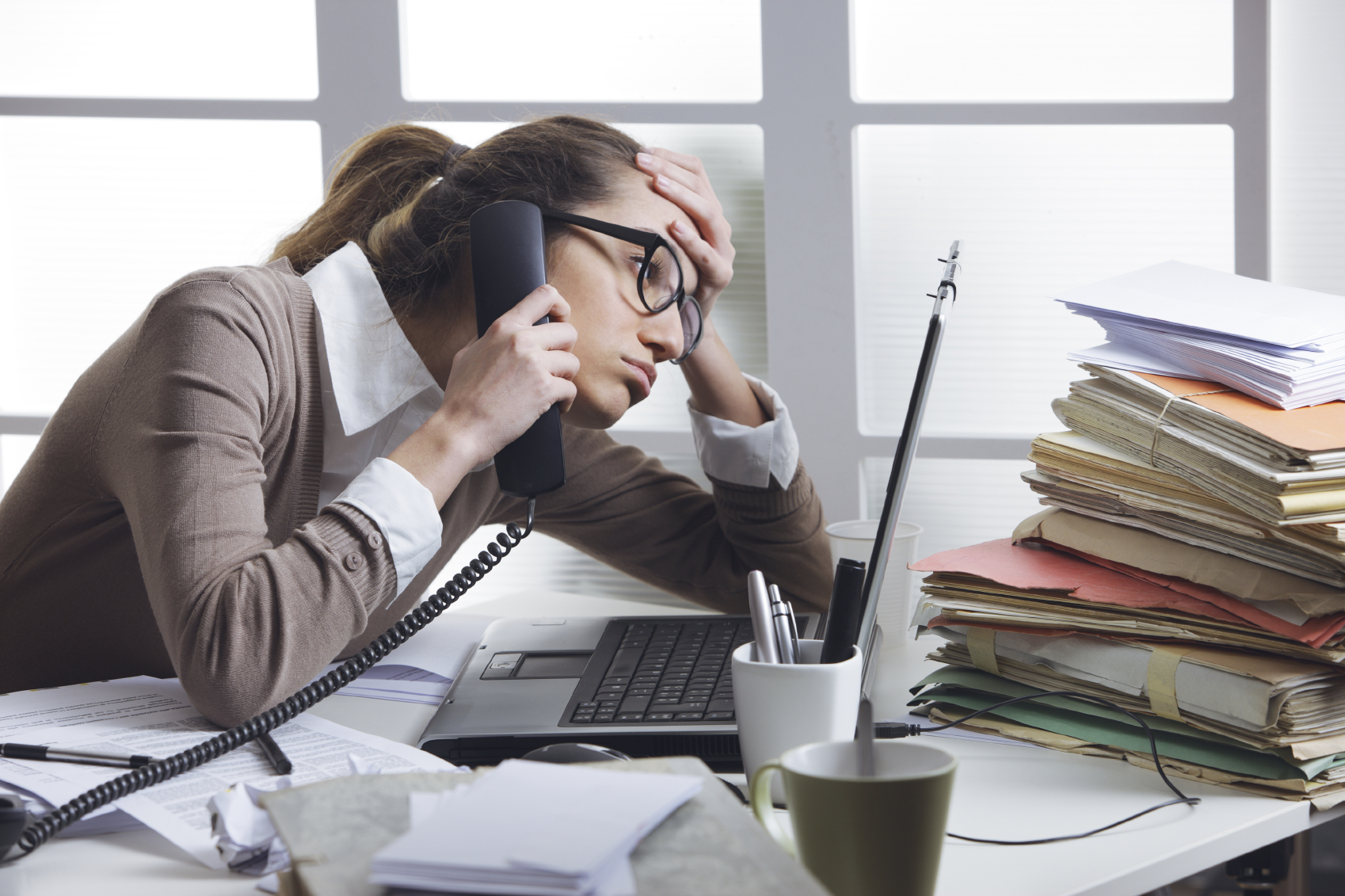 A stressed business woman looks tired  she answer telephones in her office