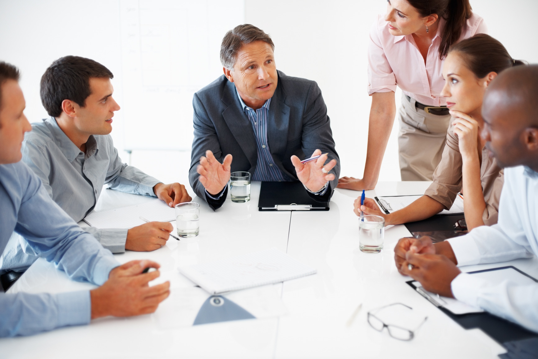 Business team listening to mature business man during meeting