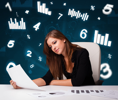 Young businesswoman sitting at desk with diagrams and statistics