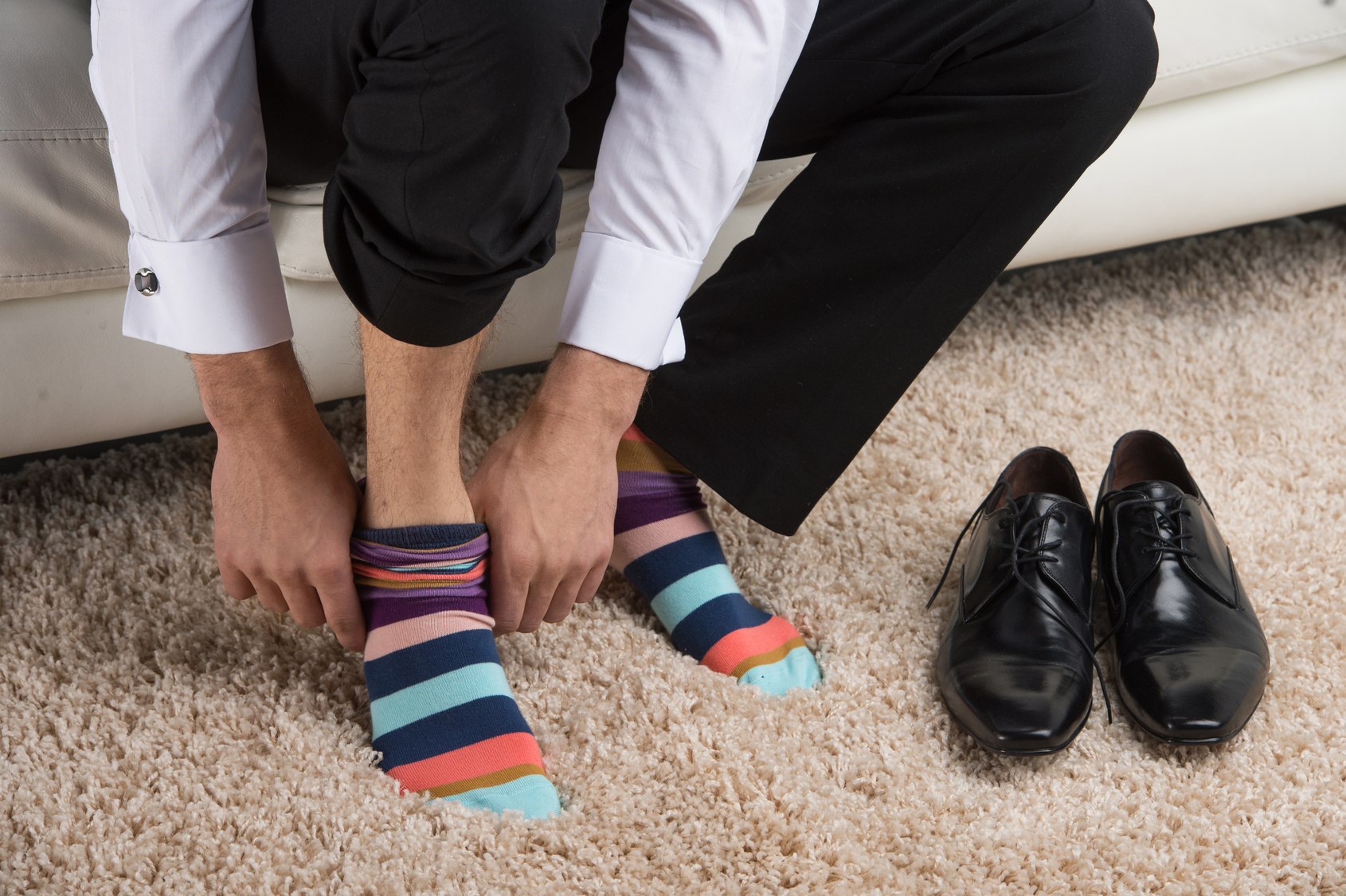 man wearing colorful sock under classical business suite.