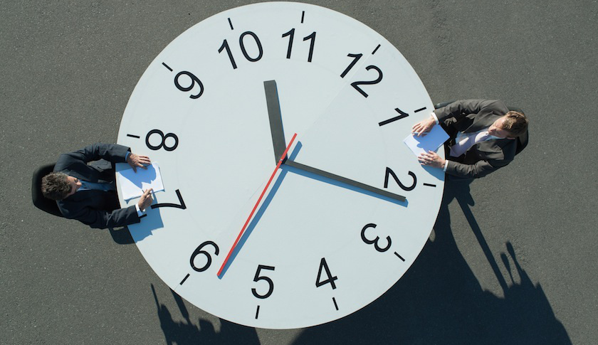 Two businessmen sitting at a clock table
